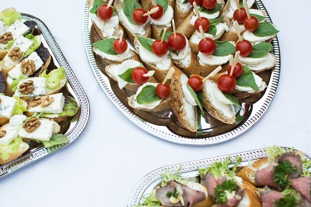 Pequeños sándwiches abiertos en fiesta en el jardín