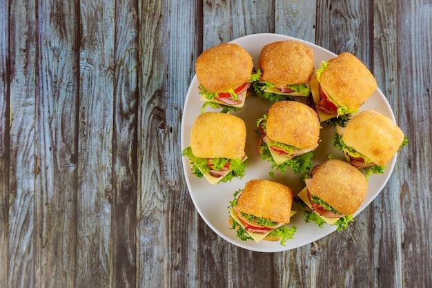 Pequeños sándwiches con jamón en plato sobre mesa de madera