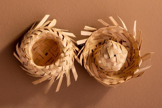 Pequeños sombreros de paja utilizados para adornos de fiesta junina sobre fondo marrón