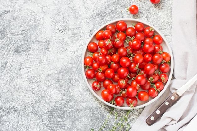 Pequeños tomates cherry (ciliegini, pachino, cóctel). grupo de tomates cherry en un hormigón gris maduros y jugosos tomates cherry
