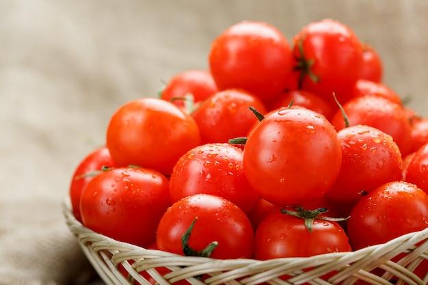 Pequeños tomates rojos en una cesta de mimbre en una vieja mesa de madera. cereza madura y jugosa