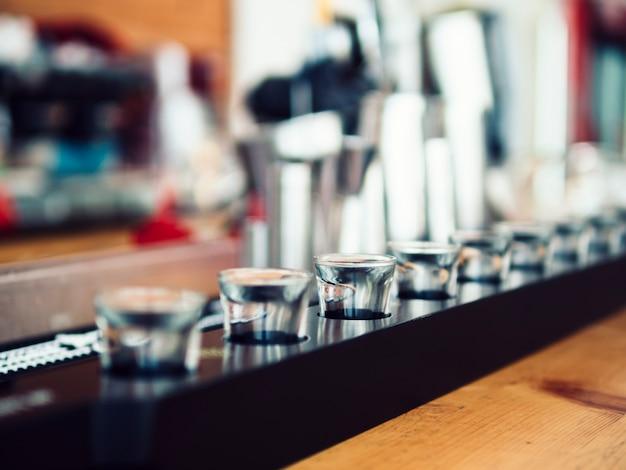 Pequeños vasos de chupito en barra de bar.