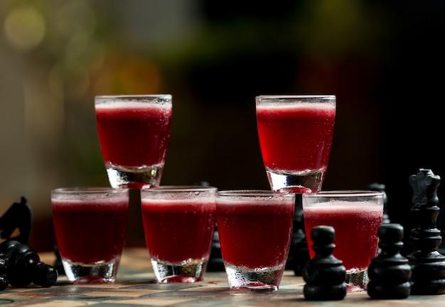 Pequeños vasos múltiples de bebidas rojas en el soporte del bar