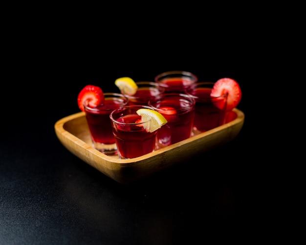 Pequeños vasos de sangría con limón y fresas dentro de bandeja de bambú en un espacio negro.