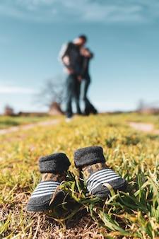 Pequeños zapatos de bebé en la hierba con una mujer embarazada y su marido en el fondo