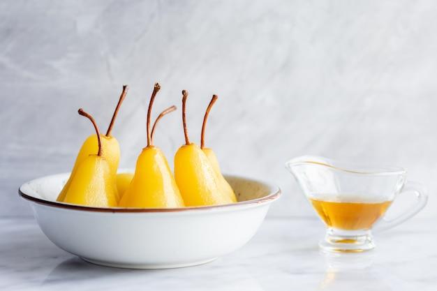 Pera caramelizada caliente con miel. postre de fruta dulce para la cena. frutas a la parrilla con hierbas. al horno con azúcar.