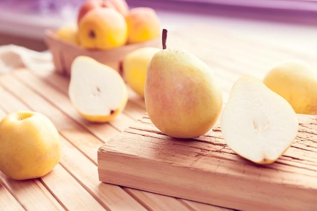 Pera y manzanas amarillas sobre una superficie de madera