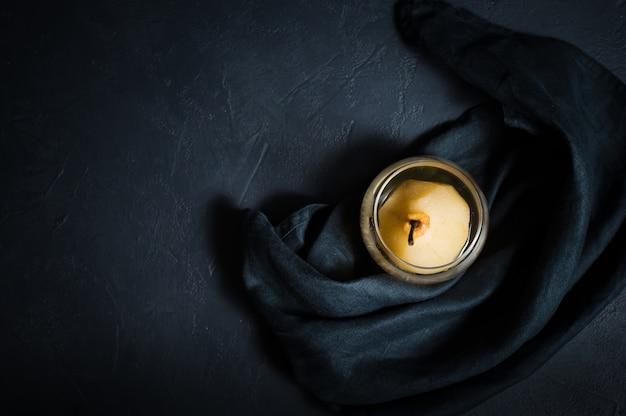 Pera pochada en un vaso.