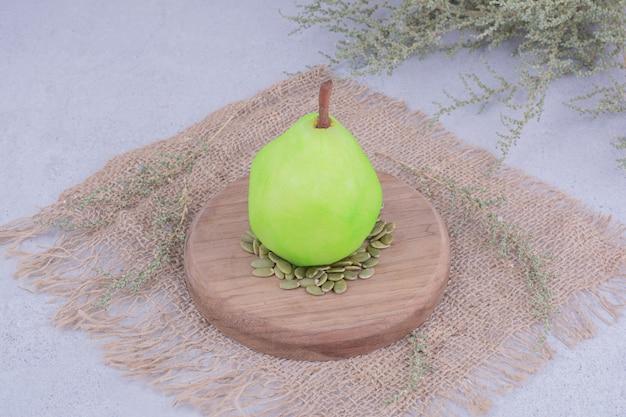Una pera verde sobre una tabla de madera con semillas de calabaza