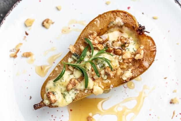 Peras al horno con queso azul, gorgonzola, miel de roquefort y nueces. menú de restaurante, dieta, receta de libro de cocina.