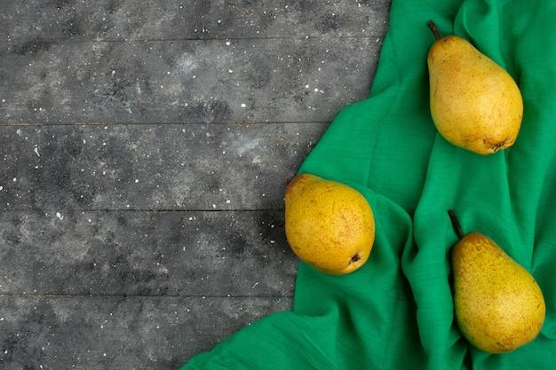 Peras amarillas maduras frescas suaves sobre un tejido verde y piso rústico claro