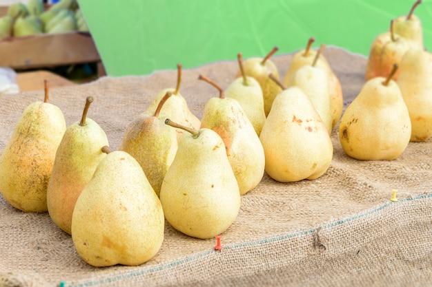 Peras amarillas orgánicas saludables en la mesa con arpillera