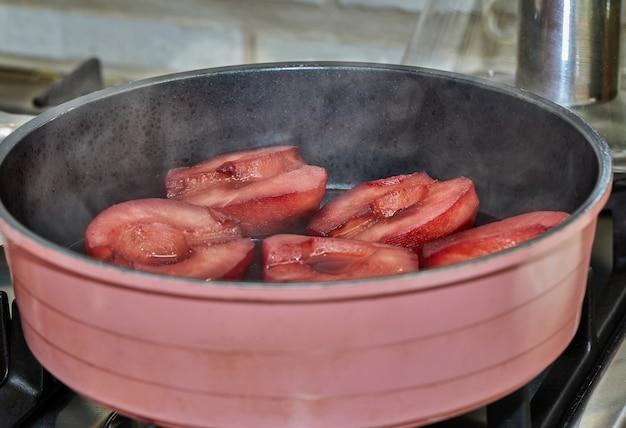 Las peras cortadas se hierven en almíbar rojo con vino en una estufa de gas.