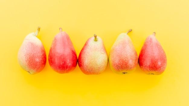 Peras enteras rojas maduras en fila