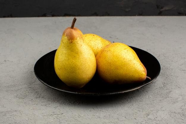 Peras frescas maduras suaves dentro de la placa negra sobre una luz