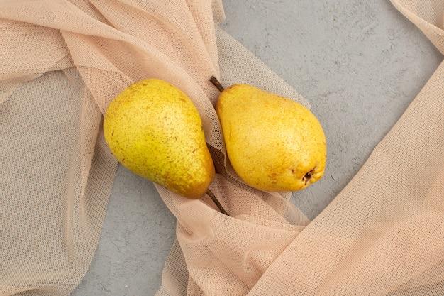 Peras frescas maduras, suaves y jugosas sobre un tejido de crema y piso gris