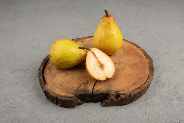 Peras frescas en rodajas y enteras sobre un escritorio de madera marrón y gris