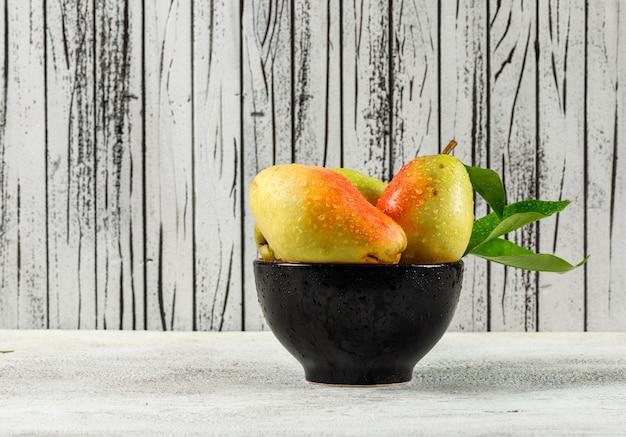Peras con hojas en un recipiente negro sobre fondo de madera y blanco sucio.