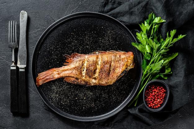 Perca de mar al horno servido en un plato redondo con perejil. fondo negro. vista superior.