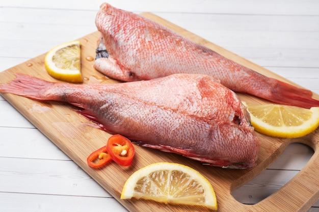 Perca de pescado crudo sin cabeza con rodajas de limón y pimientos rojos picantes sobre tabla para cortar madera
