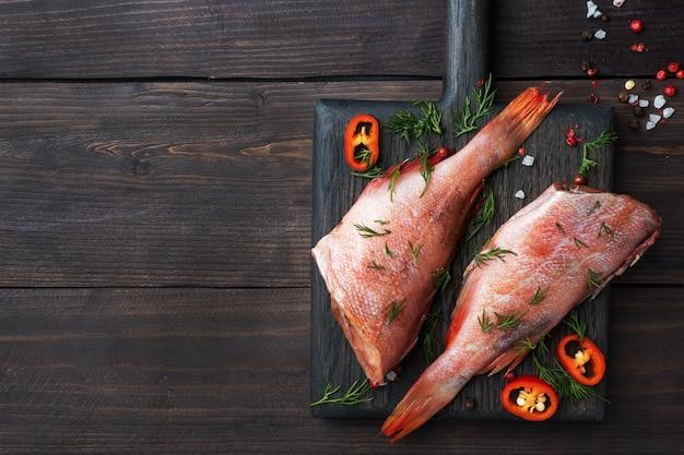 Perca de pescado crudo con eneldo y chiles en una madera.