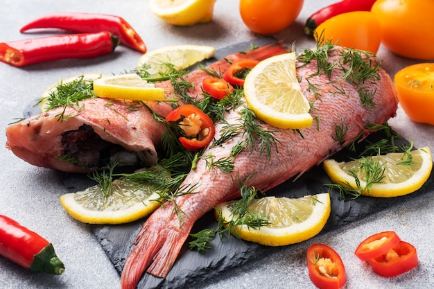 Perca de pescado crudo con limón y eneldo y chiles sobre un soporte de pizarra de hormigón.