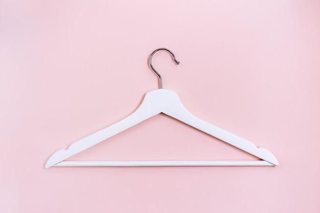 Percha blanca sobre fondo rosa