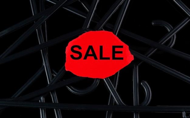 Perchas negras y venta de texto en el papel tor sobre fondo negro. descuentos. venta de temporada.