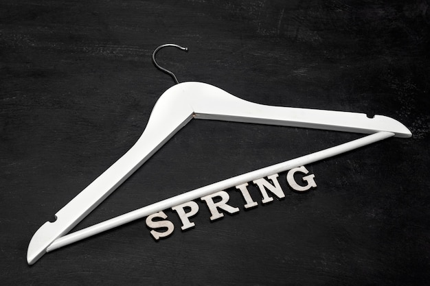 Perchero de madera blanca e inscripción primavera sobre fondo negro. colección de ropa de primavera.