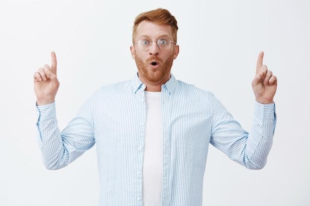 Perder palabras mientras mira un gran plan de negocios. retrato de hombre pelirrojo emocionado asombrado e impresionado con cerdas, jadeando, apuntando hacia arriba con las manos levantadas y mirando a través de gafas
