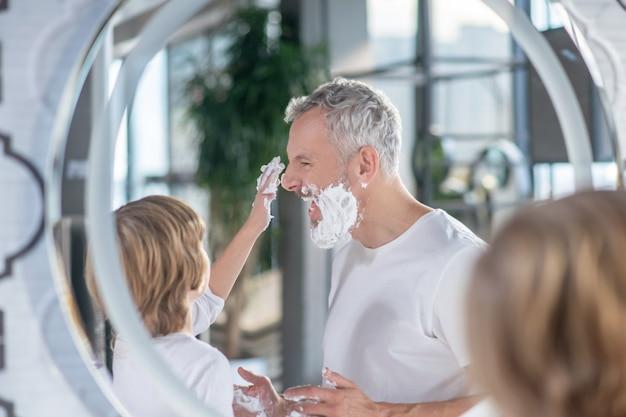 Perder el tiempo. un niño y un hombre jugando con espuma de afeitar.