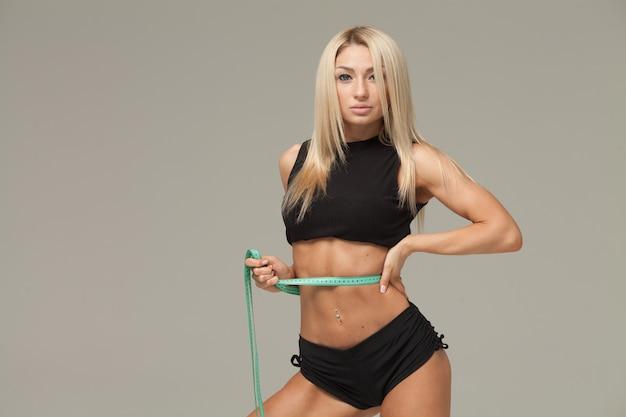 Pérdida de peso, cuerpo delgado, concepto de estilo de vida saludable. fit fitness girl midiendo su cintura con cinta métrica en gris