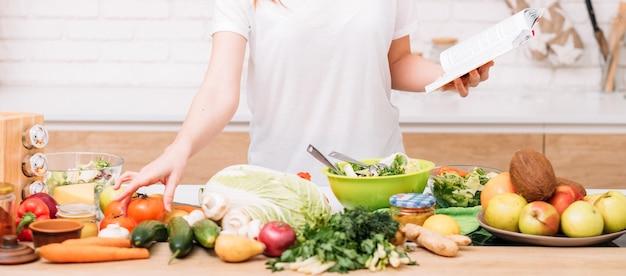 Pérdida de peso saludable y equilibrio nutricional. estilo de vida de la mujer. mujer con libro de recetas preparando ensalada. surtido de alimentos orgánicos.