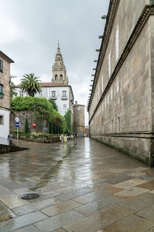Peregrinos y turistas caminando en una calle de día lluvioso del casco antiguo de santiago de compostela