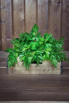 Perejil verde fresco en caja de madera en la madera vieja
