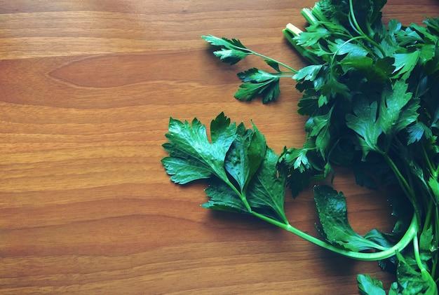 Perejil verde en el lado izquierdo de una mesa de madera
