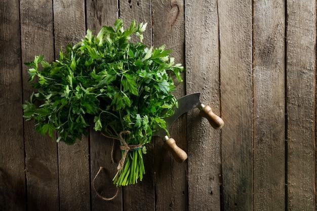 Perejil vibrante colorido fresco con el cuchillo en la tabla de madera. verano, primavera, vida sana o concepto de detox.