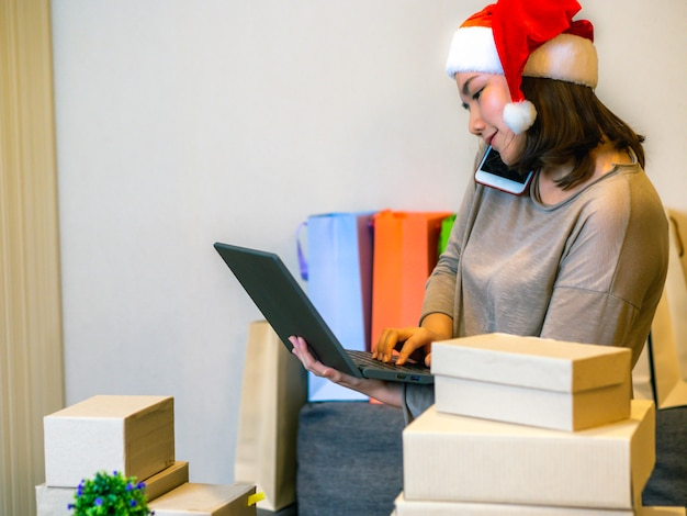 Perfeccione el concepto del vendedor en línea del negocio, mujeres asiáticas con su vendedor en línea independiente del negocio del trabajo.