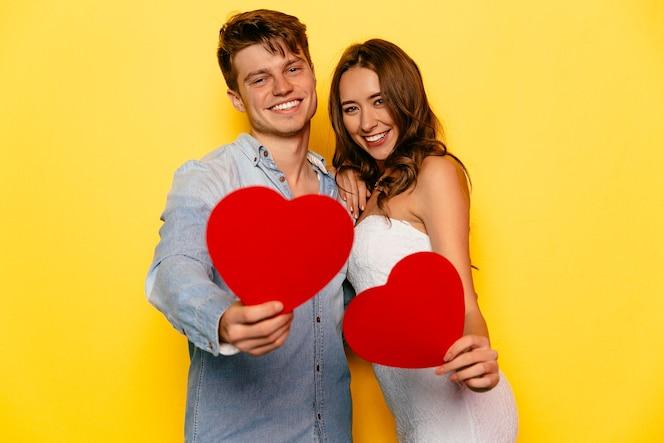 Perfecta hermosa pareja celebrando el día de san valentín, sosteniendo corazones rojos