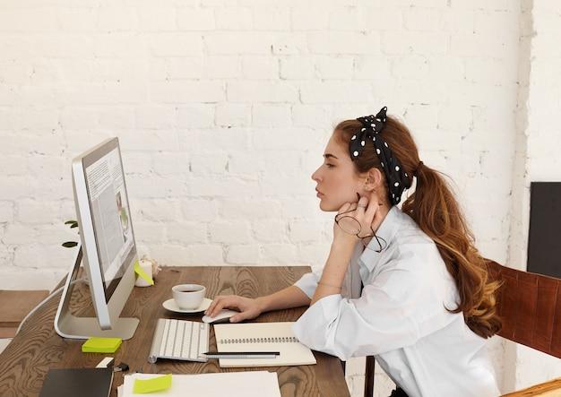 Perfil de una atractiva joven bloguera o columnista europea concentrada sentada en su lugar de trabajo frente a una computadora de escritorio, trabajando en nuevo material para su blog, taza y papelería en el escritorio