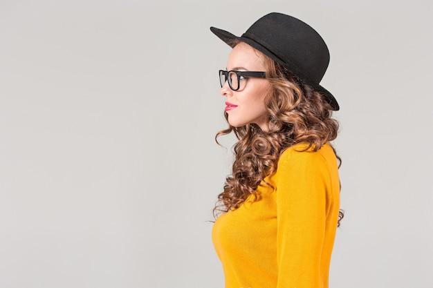 El perfil de la chica emocional con sombrero en la pared gris