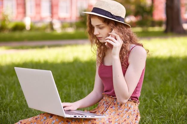 Perfil de la chica de pelo rizada pensativa ocupada que trabaja en el parque con la computadora portátil, se sienta en la hierba, busca información, habla por teléfono, se centra en sus tareas domésticas. concepto de vida estudiantil.