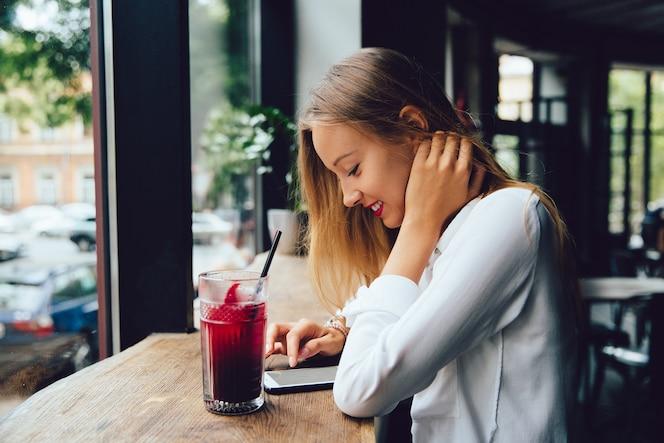 Perfil de mujer rubia joven sonriente, usando un teléfono inteligente, mensajes de texto un mensaje