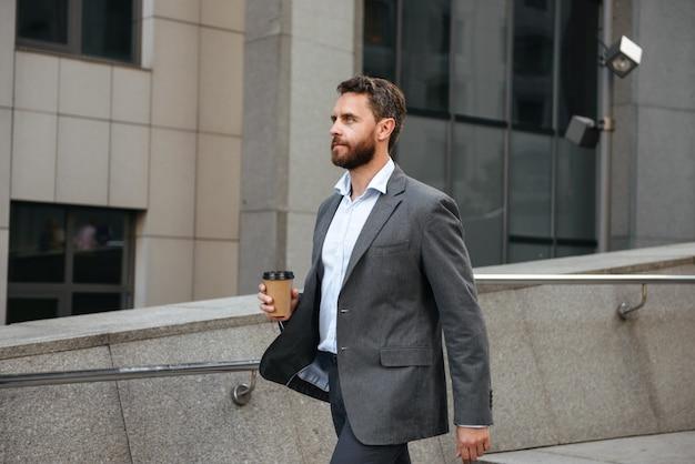Perfil de director ejecutivo exitoso o empresario en traje gris con café para llevar y caminando por la calle con un moderno centro de negocios