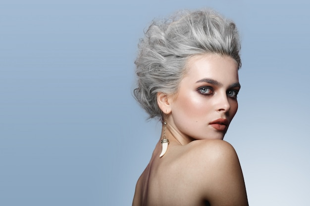 Perfil de hermosa joven modelo con peinado gris, hombros desnudos, maquillaje, ojos ahumados, aislado sobre fondo azul.