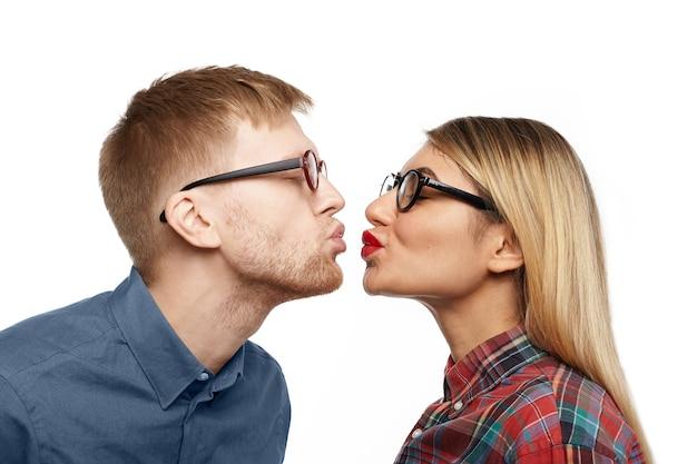 Perfil de hermosa joven rubia con elegantes lentes y lápiz labial rojo de pie frente a un chico geek barbudo, ambos haciendo pucheros y cerrando los ojos para besarse