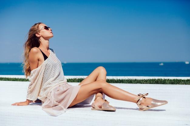 Perfil de una hermosa modelo en gafas de sol, con ropa elegante, sentado en el banco
