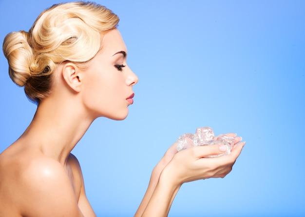 Perfil de hermosa mujer joven con hielo en sus manos en azul