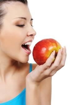 Perfil de hermosa niña comiendo una manzana - aislado en blanco