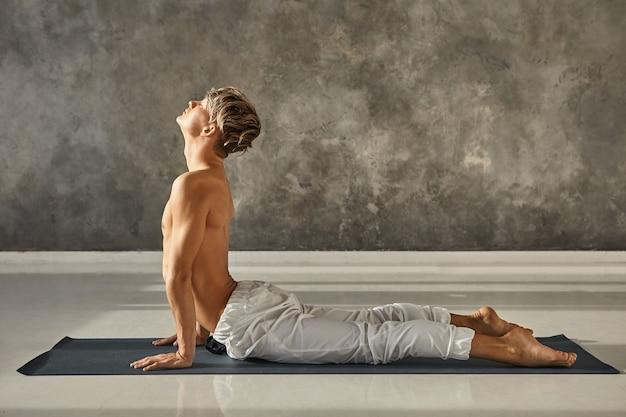Perfil de hombre caucásico joven musculoso practicando yoga en el gimnasio, haciendo estiramiento para el pecho y el abdomen en urdhva mukha shvanasana o pose de perro mirando hacia arriba para columna flexible, manteniendo los ojos cerrados